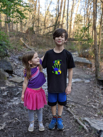 Juniper in a purple shirt and pink skirt with her arm around her brother, Cade, in a black tshirt and blue athletic shorts posing on a hiking trail