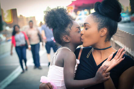 Photograph of black mother kissing her young daughter who is on her hip on the cheek